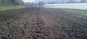 Campo arado y preparado para sembrar de la finca Catasol. Al fondo, un inverndadero.