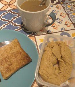Desayuno compuesto por tostada de pan integral y mantequilla de cacahuetes, con café con leche vegetal.